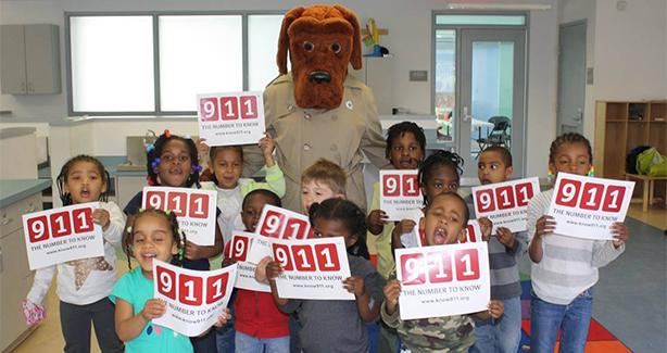 Kids holding 911 signs with Crime Dog