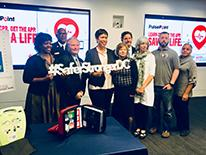 Mayor Bowser with a group of people, holding a #SaferStrongerDC sign